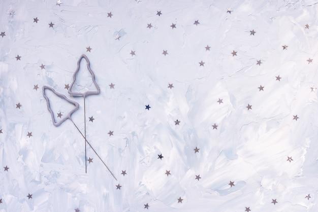 青い冬の休日の背景に輝きと銀の紙吹雪の星。お祝いの抽象的な背景
