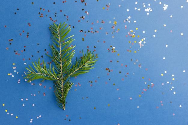青いトレンディな背景にモミの木の枝で輝きます。プロジェクトのお祝いの背景。フラットレイスタイル。上面図。今年の色。