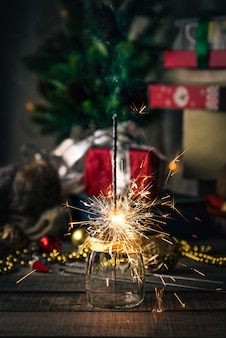 Sparkling bengal lights, christmas tree, decorations on wood