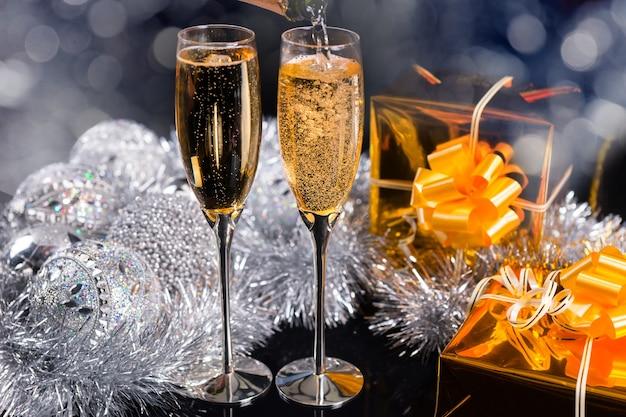 お祝いの背景に銀の装飾と金色の贈り物を備えた2つのエレガントなフルートのクリスマスのスパークリングシャンパン