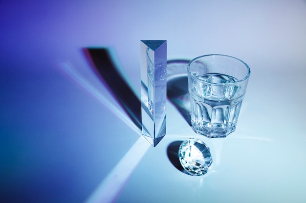 Sparkling diamond; prism; glass of water with shadow on dark blue background