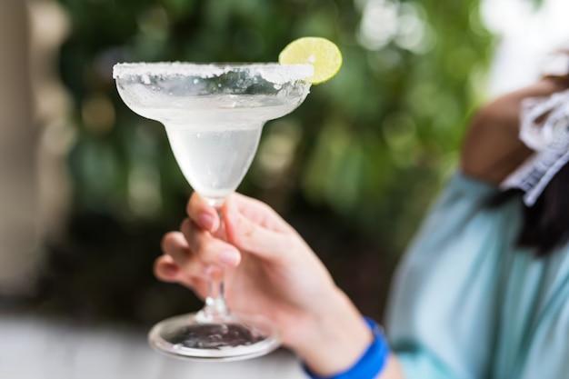 젊은 여성의 유리에 알코올, 소다, 얼음, 레몬의 스파클링 음료. 편안한 분위기의 휴가 또는 여행 휴가.