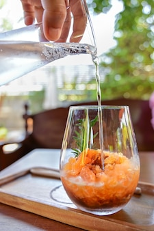 Sparkling espresso with orange granita pouring soda water over coffee mixed with orange granita