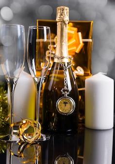 きらめくお祭りの静物-エレガントなメガネ、白い柱のキャンドル、金で包まれたギフトに囲まれたシャンパンボトルの首からぶら下がっているアンティーク懐中時計