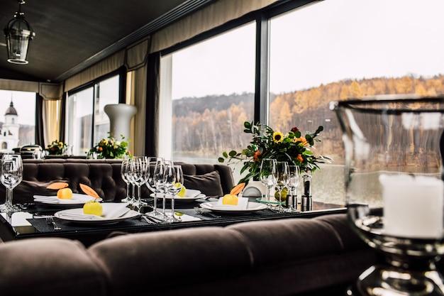 결혼식 저녁 식사를 위해 준비된 긴 테이블에 스파클링 유리 제품 스탠드