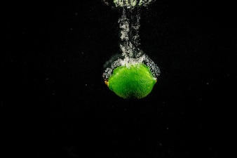 Sparkling green lime splashes water on black background