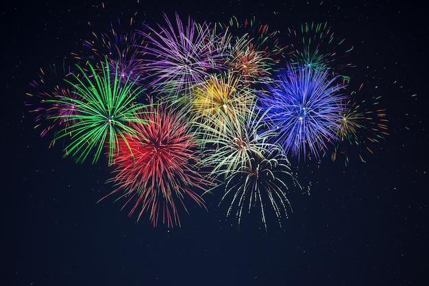 星空に輝く紫、緑、赤、青、黄色のお祝い花火。独立記念日、7月4日、年末年始は背景に敬礼します。