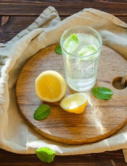 Sparkling water in glass with cutting board, leaves and lemon
