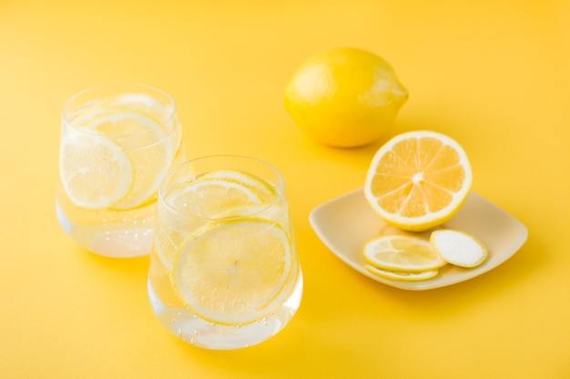 Sparkling water with lemon and ice in glasses and lemon slices on a saucer on a yellow table.