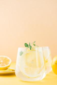 黄色いテーブルの受け皿にレモン、メリッサ、氷をグラスに入れ、レモンスライスを入れたスパークリングウォーター。アルコール飲料ハードセルツァー。閉じる。垂直方向のビュー