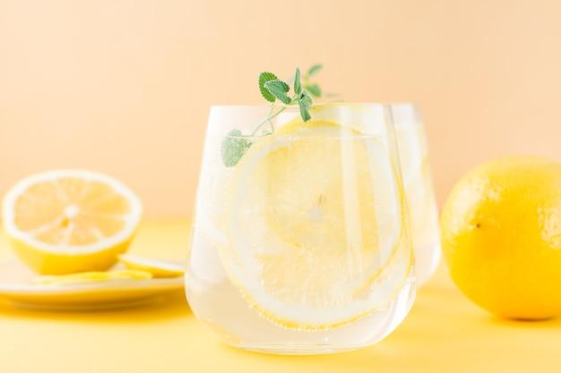 黄色いテーブルの受け皿にレモン、メリッサ、氷をグラスに入れ、レモンスライスを入れたスパークリングウォーター。アルコール飲料ハードセルツァー。閉じる