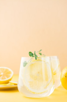 Sparkling water with lemon, melissa and ice in glasses and lemon slices on a saucer on a yellow table. alcoholic drink hard seltzer. close-up. vertical view