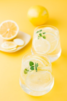 Sparkling water with lemon, melissa and ice in glasses and lemon slices on a saucer on a yellow table. alcoholic drink hard seltzer. vertical view