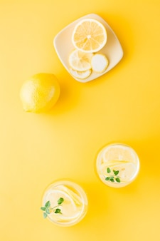 Sparkling water with lemon, melissa and ice in glasses and lemon slices on a saucer on a yellow table. alcoholic drink hard seltzer.