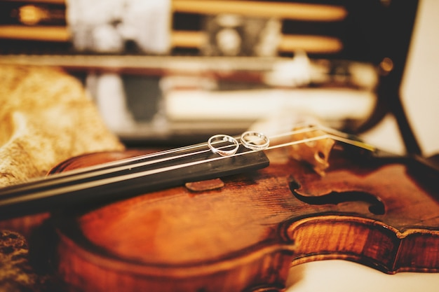 Sparkling wedding rings lie on the violin strings