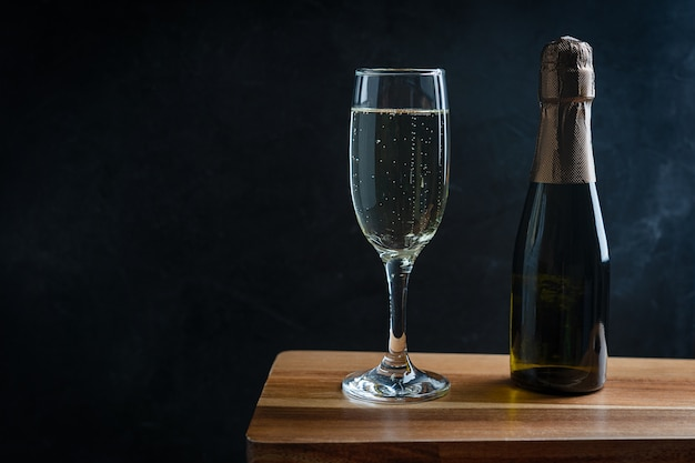Sparkling white champagne served in flute glass with small bottle on dark wooden table