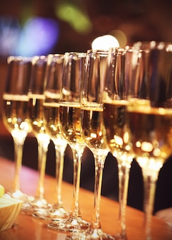 Sparkling wine glasses champagne stand in row at the bar, catering