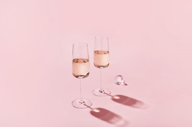 Sparkling wine glasses on colored pink background with sharp shadows