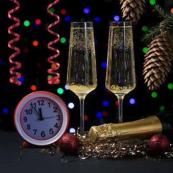 Sparkling wine glasses red streamers and red clock. happy new year