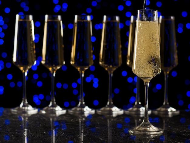 Игристое вино наливают в бокал напротив ряда полных бокалов. популярный алкогольный напиток.