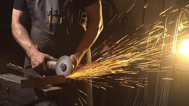 금속 앵글 그라인더 절단 중 불꽃. 산업 분쇄기를 사용하여 작업자입니다.