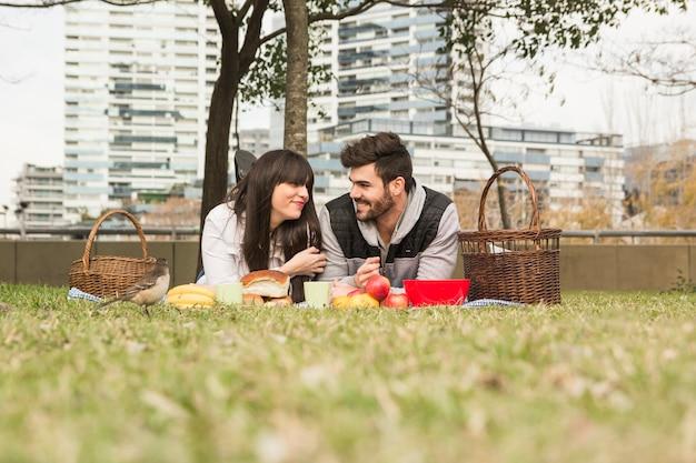공원에서 피크닉을 즐기는 젊은 부부 앞에서 참새