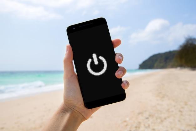 Spartphone с выключенным знаком на экране в женской руке на пляже