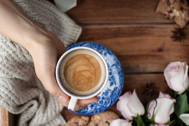 Ароматный кофе в женской руке, букет белых роз и осенний уют. доброе утро. вид сверху. скопировать spase.