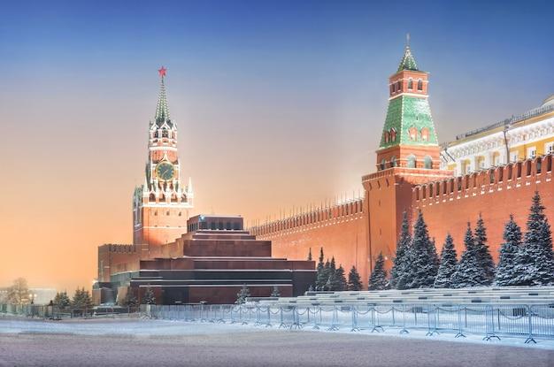 Спасская башня и мавзолей в московском кремле и ели под снегом при свете вечерних фонарей
