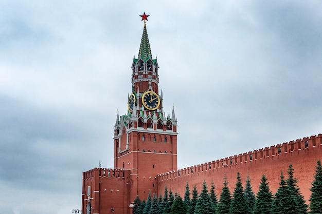 Спасская башня кремля с красивыми голубыми елями на красной площади в москве на фоне хмурого неба.