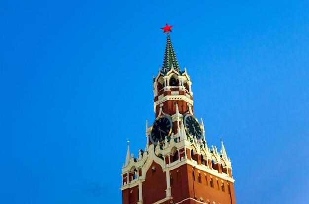 Спасская башня московского кремля с часами-куранцами на фоне вечернего неба.