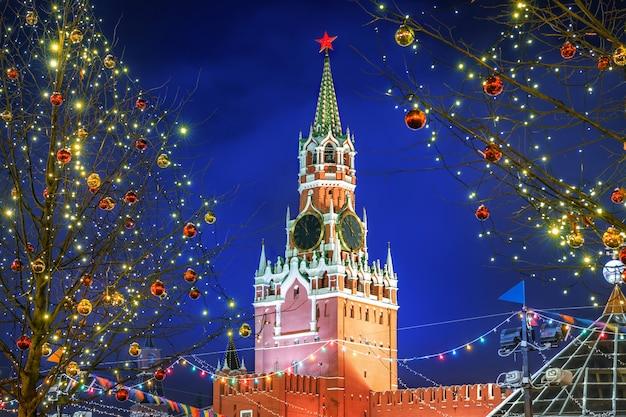 Спасская башня на красной площади в москве среди новогодних елок, украшенных шарами, в зимнюю ночь