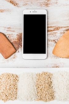 Spatula and mobile phone over the variety of rice on white tray