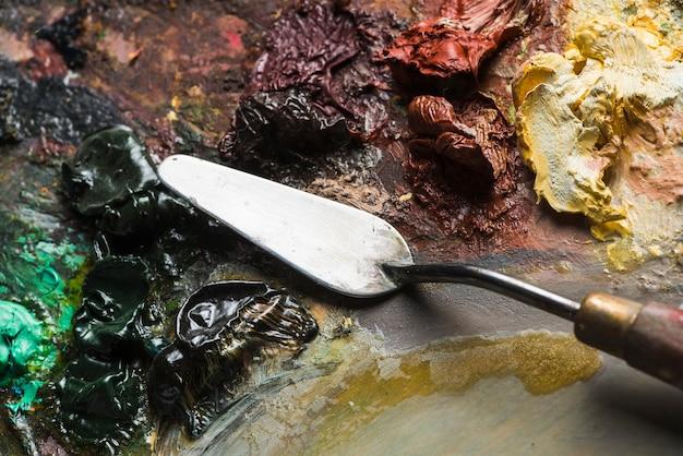 Spatula mixing paint on palette
