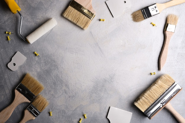 Spatulas for application of putty and brushes and rollers for painting on a gray concrete background.top view