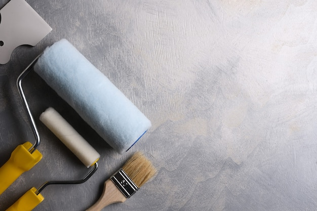 Spatulas for application of putty and brushes and rollers for painting on a gray concrete