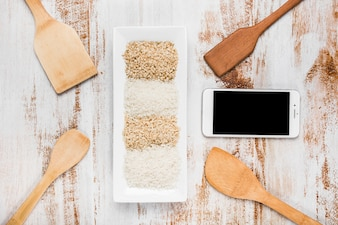 Spatulas; cell phone and tray with variety of rice on grunge background