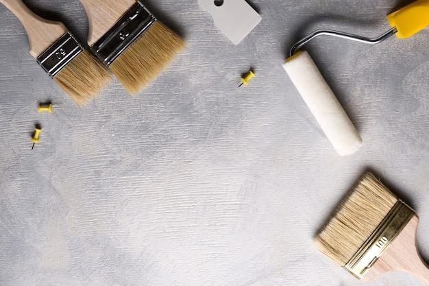 灰色のコンクリート背景にペイントするためのパテとブラシとローラーの塗布用へら。