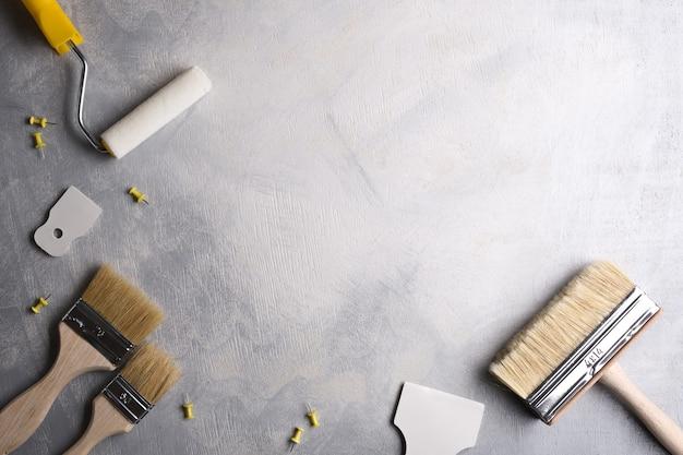 灰色のコンクリートの背景にペイントするためのパテとブラシとローラーを適用するためのスパチュラ。上面図