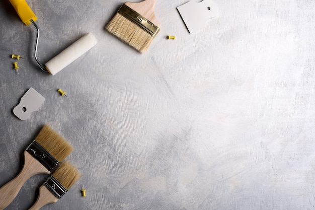灰色のコンクリートに塗るためのパテとブラシとローラーを適用するためのへら。上面図。フラットレイ