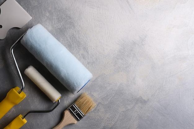 灰色のコンクリートに塗るためのパテとブラシとローラーを適用するためのヘラ