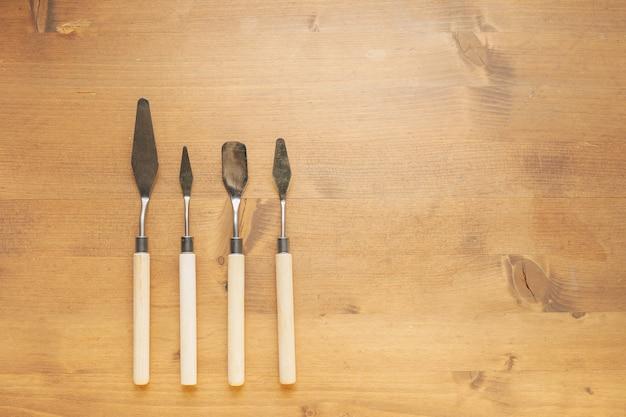 Шпатели для лепки из глины и пластилина на деревянном фоне