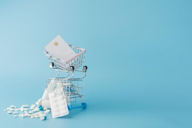 青色の背景にさまざまな薬、薬、spay、ボトル、温度計、注射器、空のショッピングトロリーカートが散在しています。薬局ショッピングコンセプト