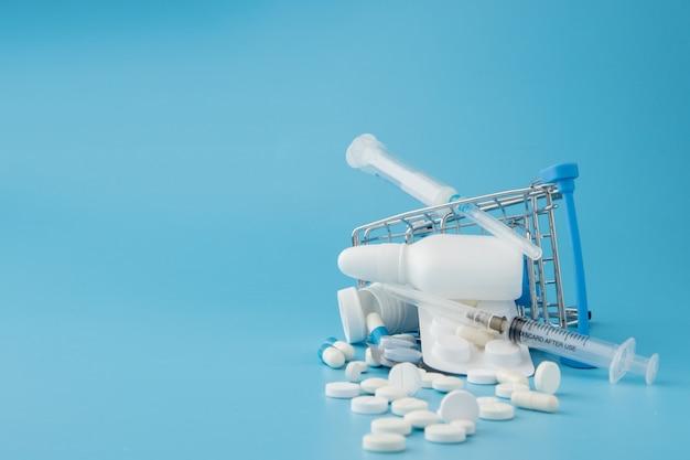 青色の背景にさまざまな薬、薬、spay、ボトル、温度計、注射器、空のショッピングトロリーカートが点在しています。薬局ショッピングコンセプト