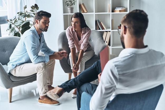Высказаться. молодая супружеская пара разговаривает, сидя на сеансе терапии с психологом