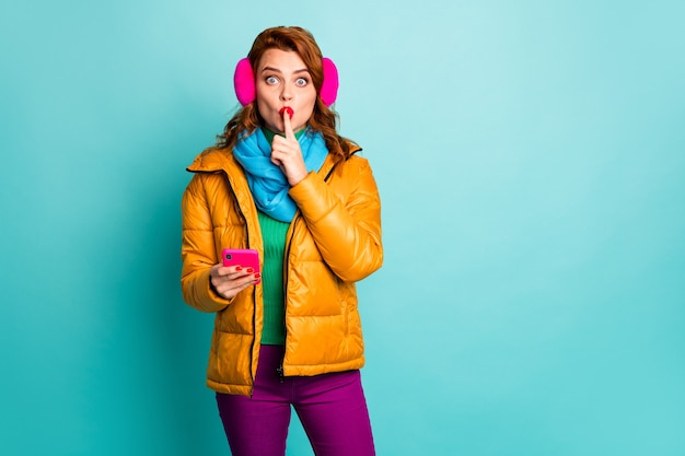 Don't speak! portrait of funny lady hold telephone finger on lips tell secret information ask to keep silence wear ear muffs yellow overcoat scarf pants.