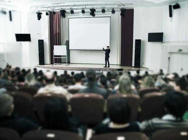 비즈니스 컨퍼런스 및 프레젠테이션에서 스피커. 컨퍼런스 홀을 청취하십시오.
