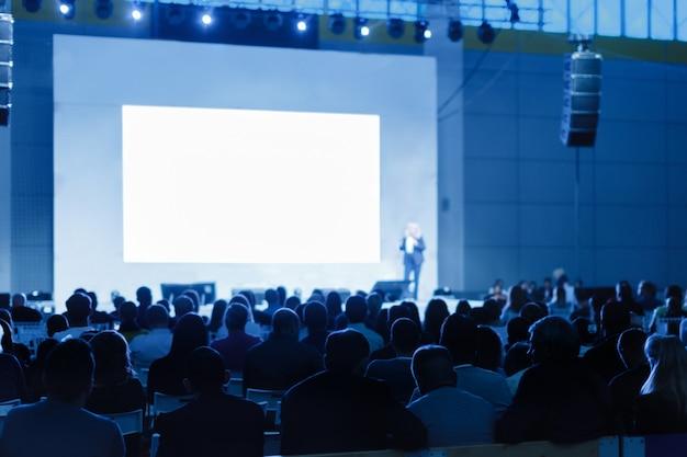 비즈니스 회의에서 연설을하는 스피커. 컨퍼런스 홀의 청중. 파란색 색조 사진 인식 할 수없는 사람에 초점