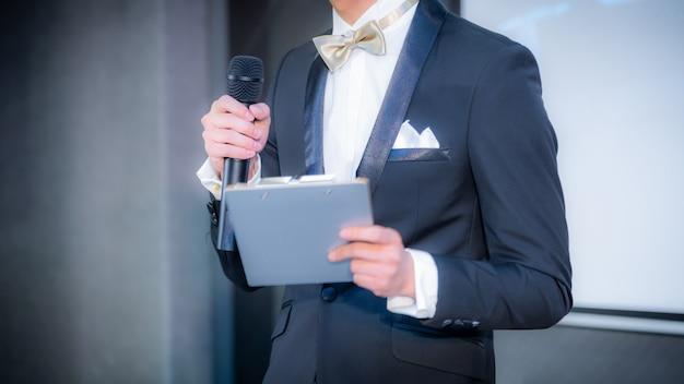 ビジネスイベントで会議ホールで講演を行うスピーカー