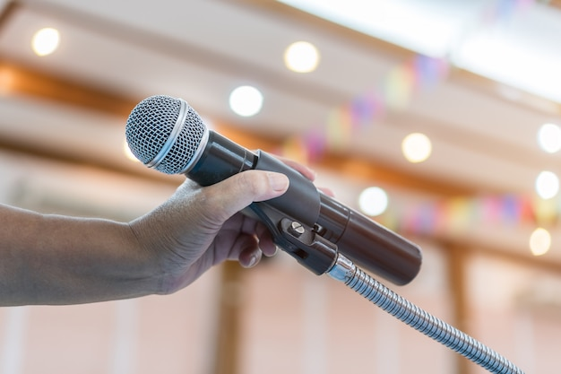 Speaker holding microphone for speak, presentation on stage in public conference seminar room.